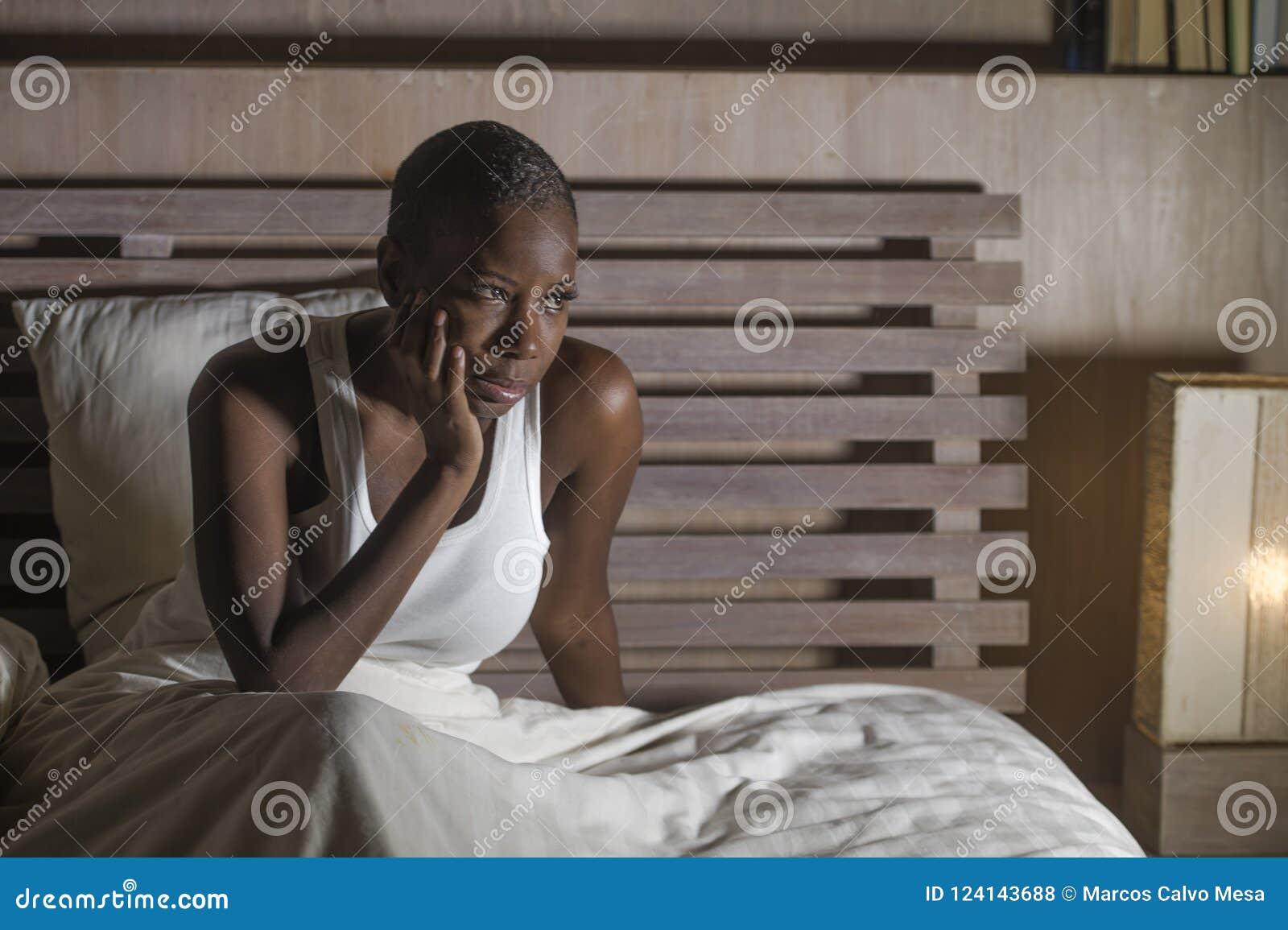 Молодая унылая подавленная черная Афро-американская женщина в инсомнии проблемы депрессии бессонного чувства кровати отчаянной по