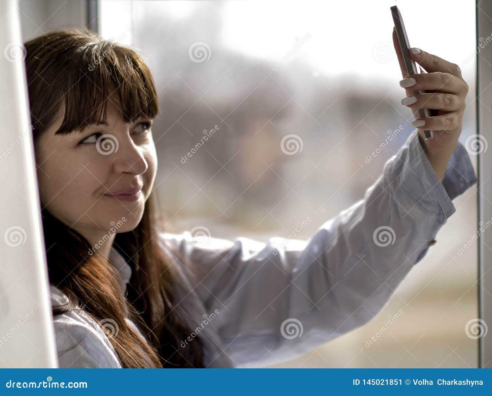 Молодая усмехаясь девушка брюнета в голубой рубашке делает selfie окном