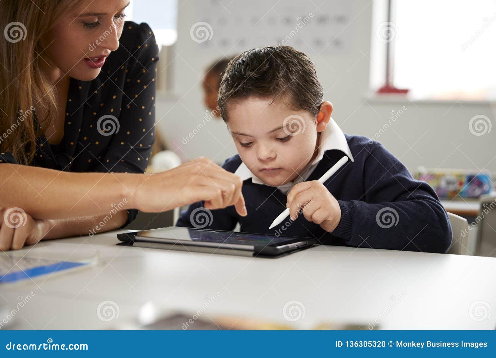 Молодая учительница работая со школьником Синдрома Дауна сидя на столе используя планшет в классе начальной школы,