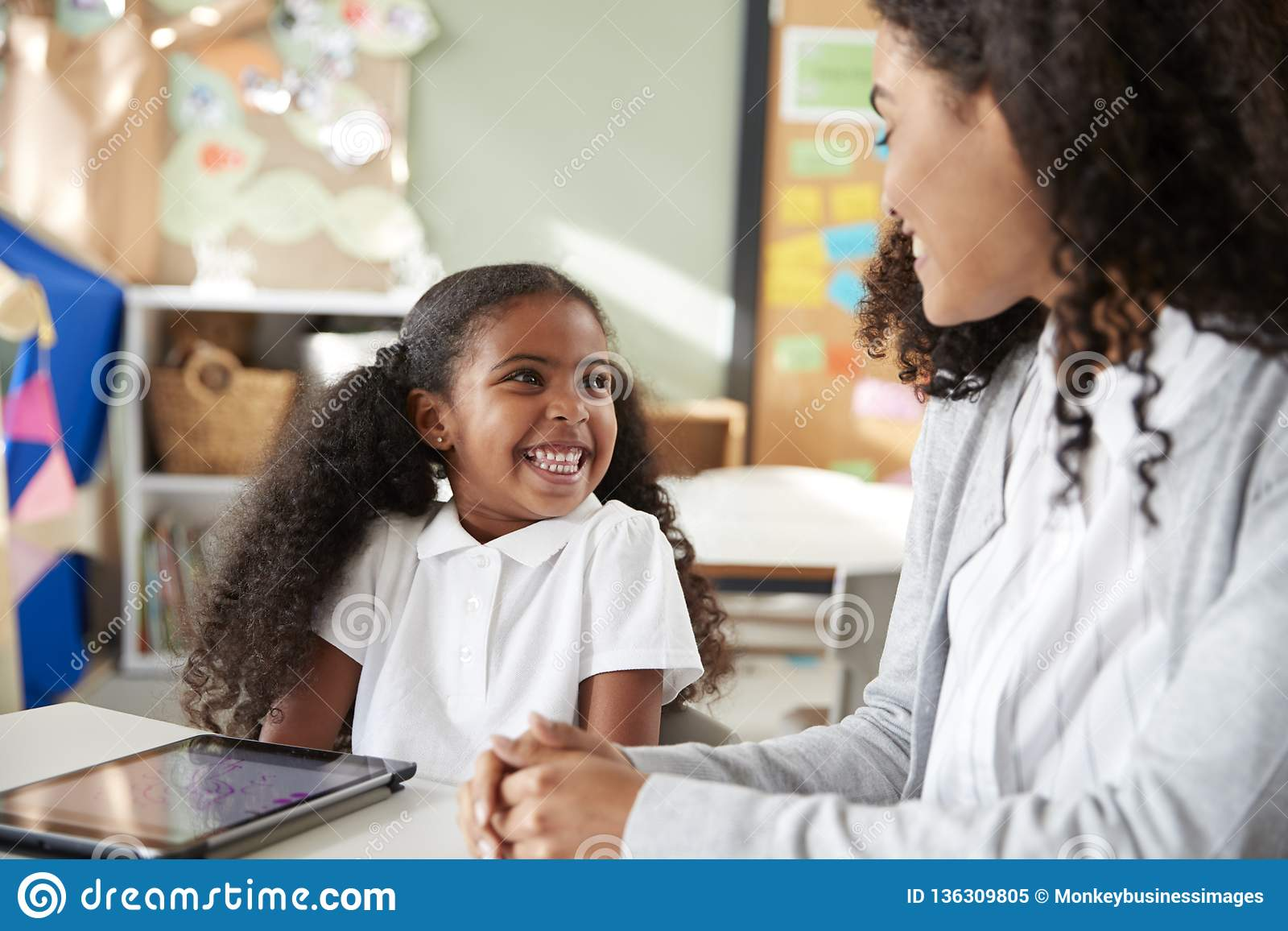 Молодая черная школьница сидя на таблице с планшетом в классе младенческой школы уча одно на одном с женским чаем