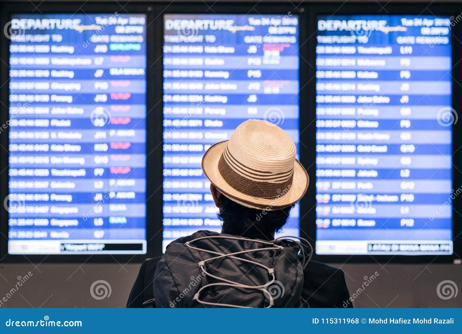 Молодое взрослое туристское backpaker путешественника смотря расписание расписания полетов авиапорта на экране