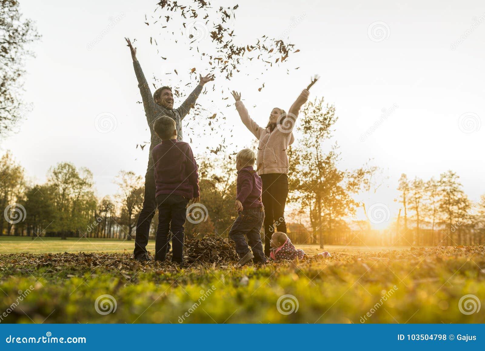 Молодое ликование семьи в восходе солнца осени