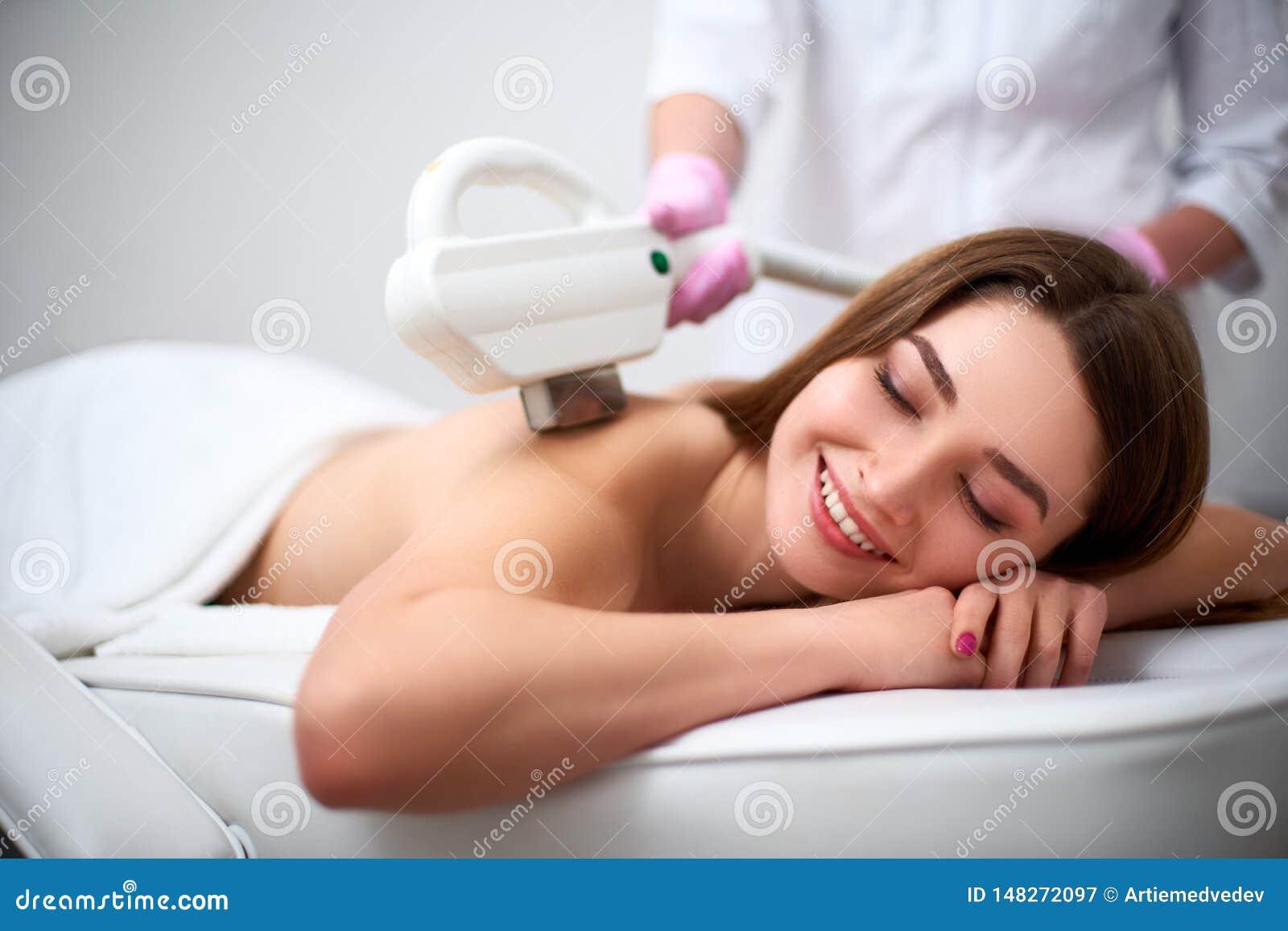 Молодое милое усмехаясь epilation лазера задней части женщины в салоне красоты Cosmetologist делая обработку депиляции с elos
