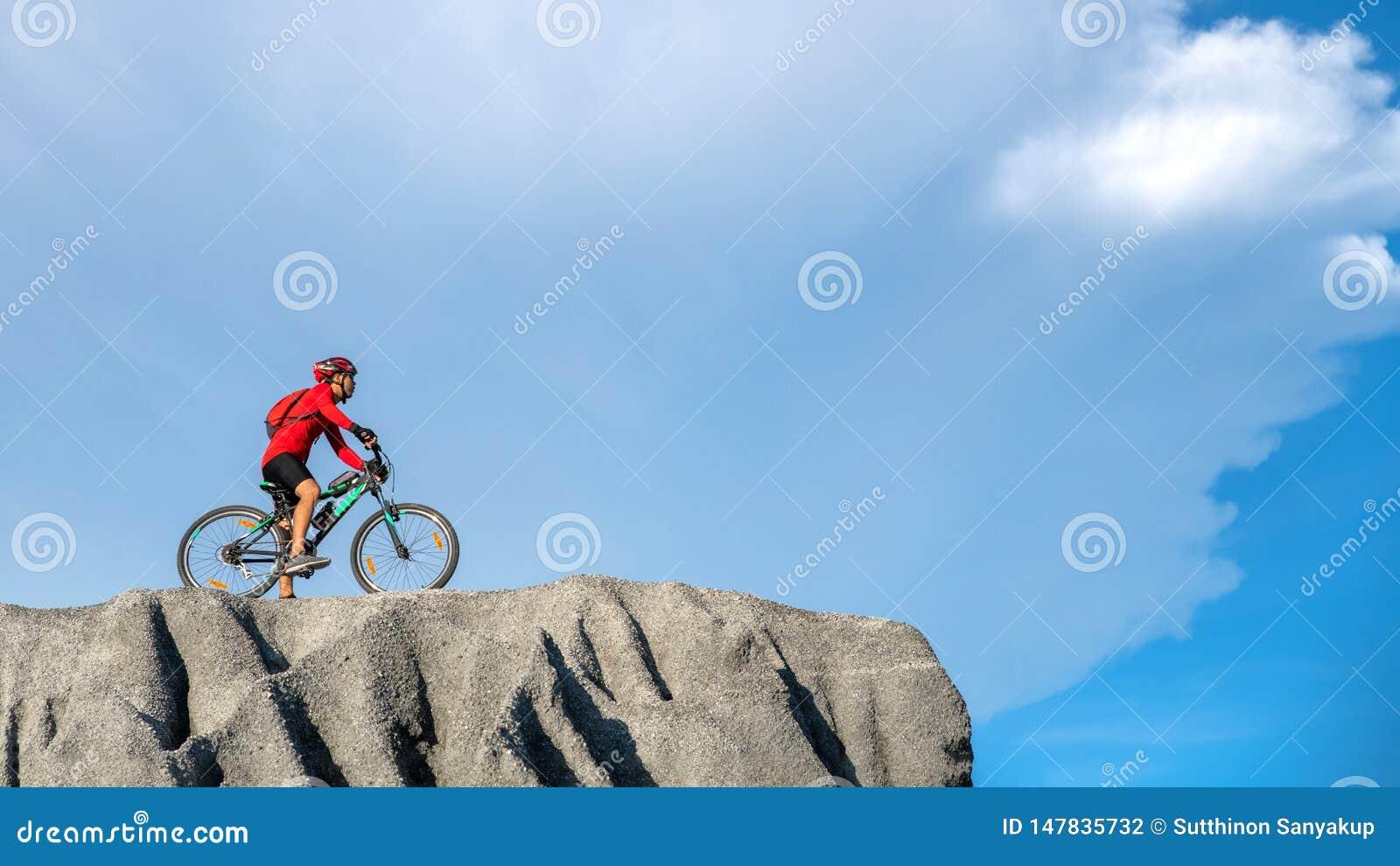 Молодое положение спортсмена на утесе с велосипедом Горный велосипед катания велосипедиста на скалистом следе на заходе солнца Ве