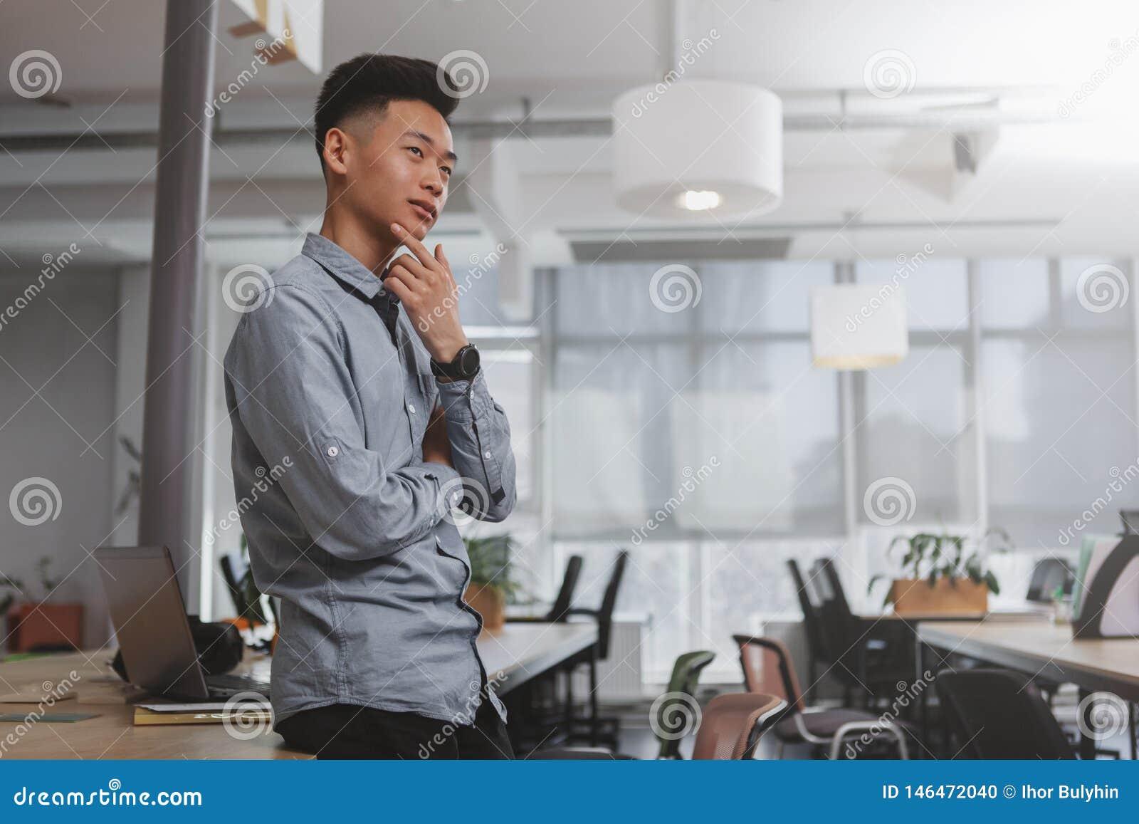 Молодой азиатский бизнесмен работая на офисе