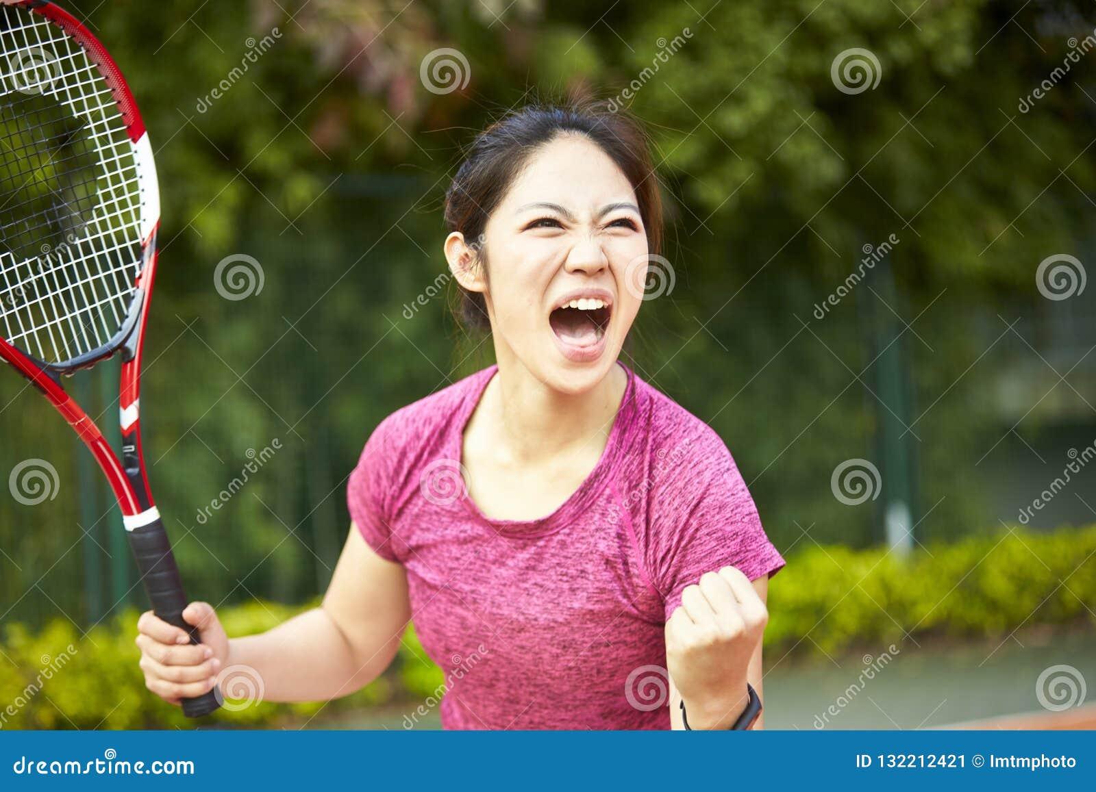 Молодой азиатский женский теннисист празднуя после вести счет