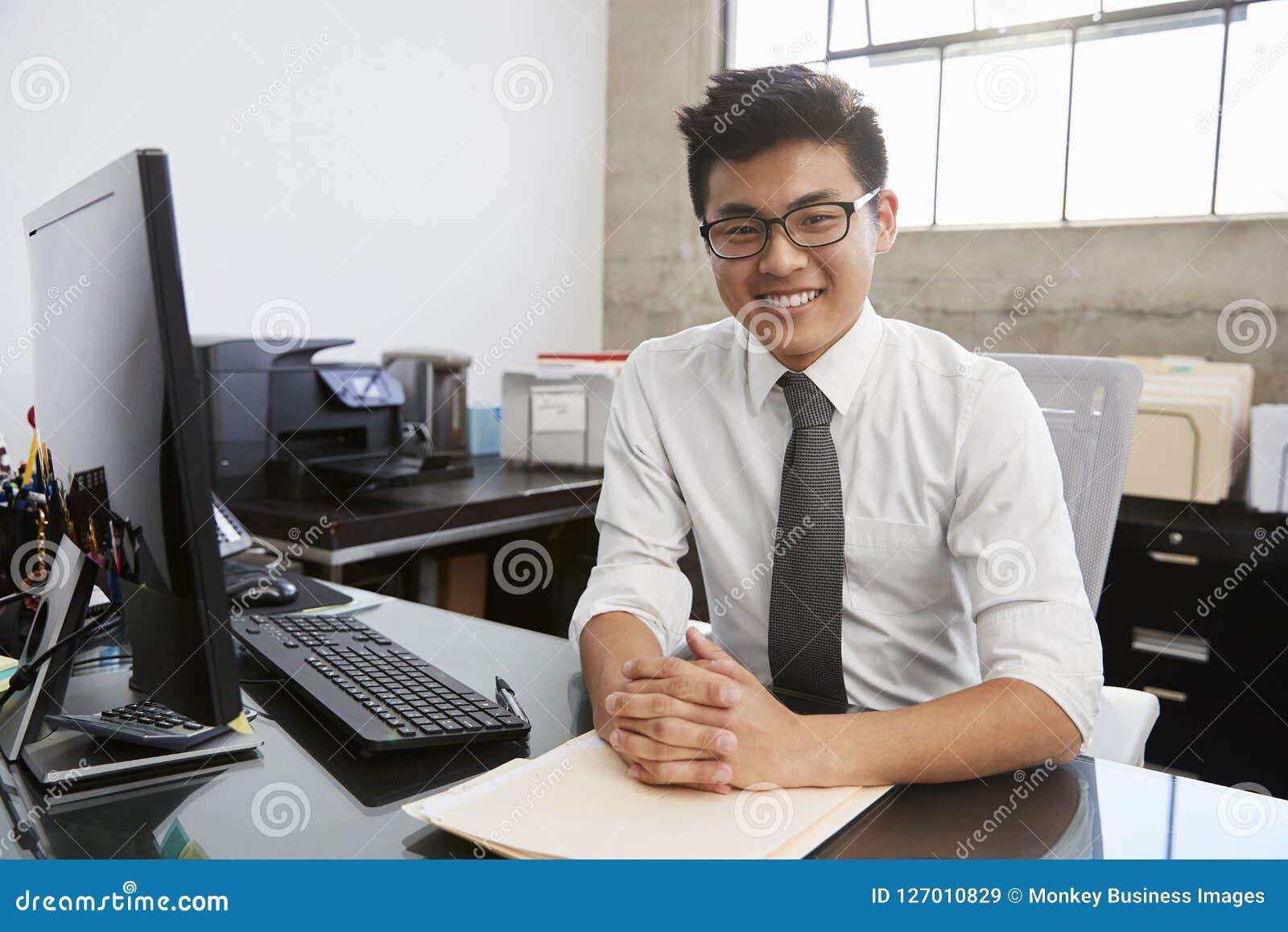 Молодой азиатский мужской профессионал на столе усмехаясь к камере