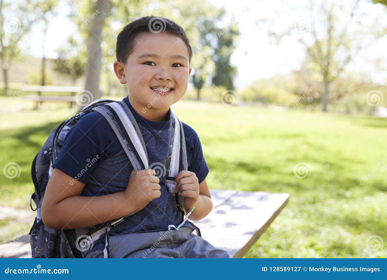 Молодой азиатский школьник с рюкзаком усмехаясь к камере