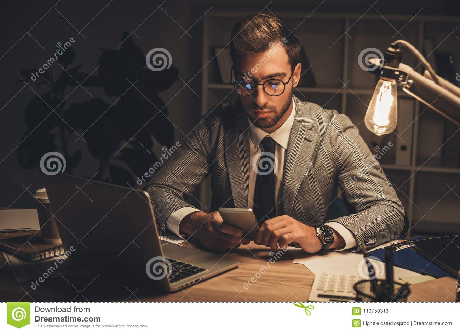 молодой бизнесмен используя smartphone на поздно