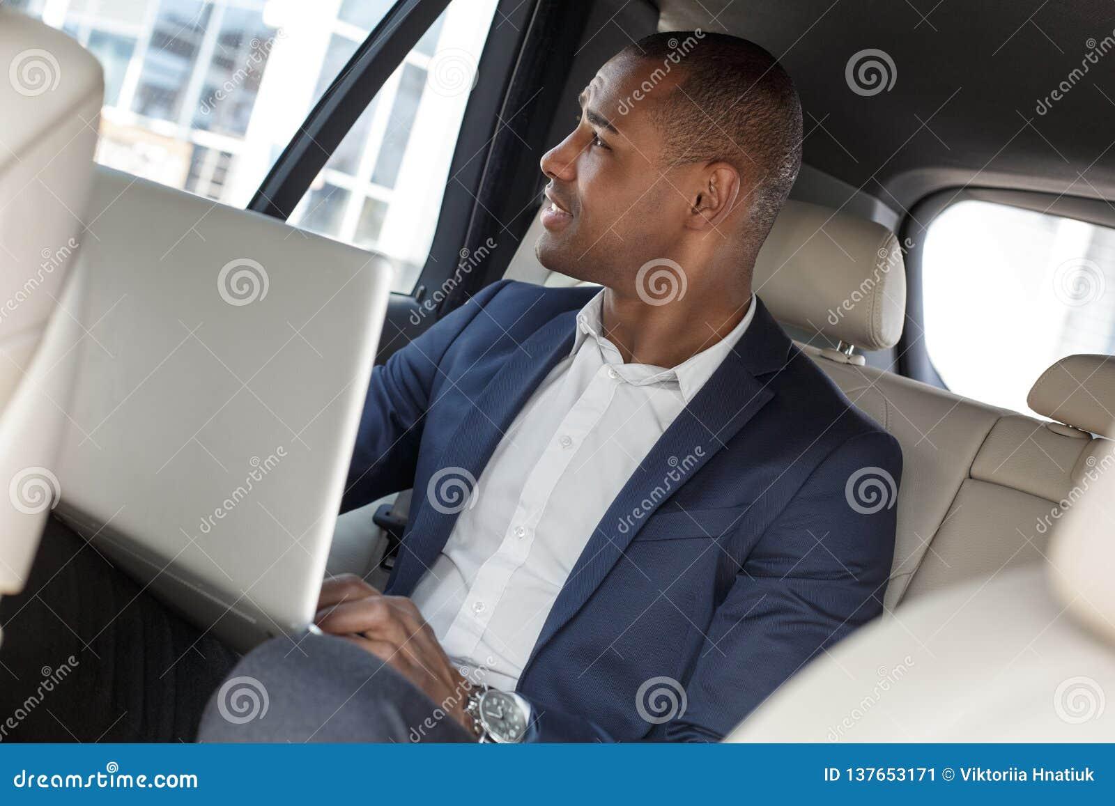 Молодой бизнесмен сидя на заднем сидении в деятельности автомобиля на ноутбуке смотря вне окно внимательное