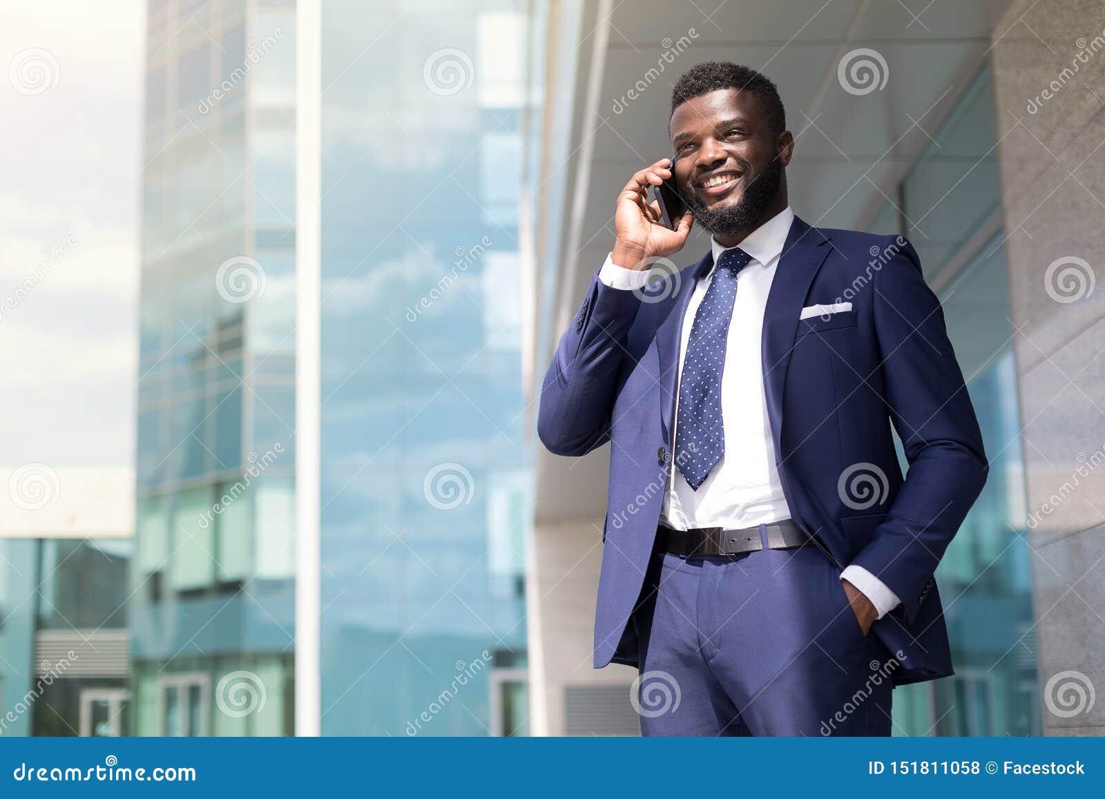 Молодой бизнесмен с бородой в голубом костюме говоря по телефону снаружи с космосом экземпляра