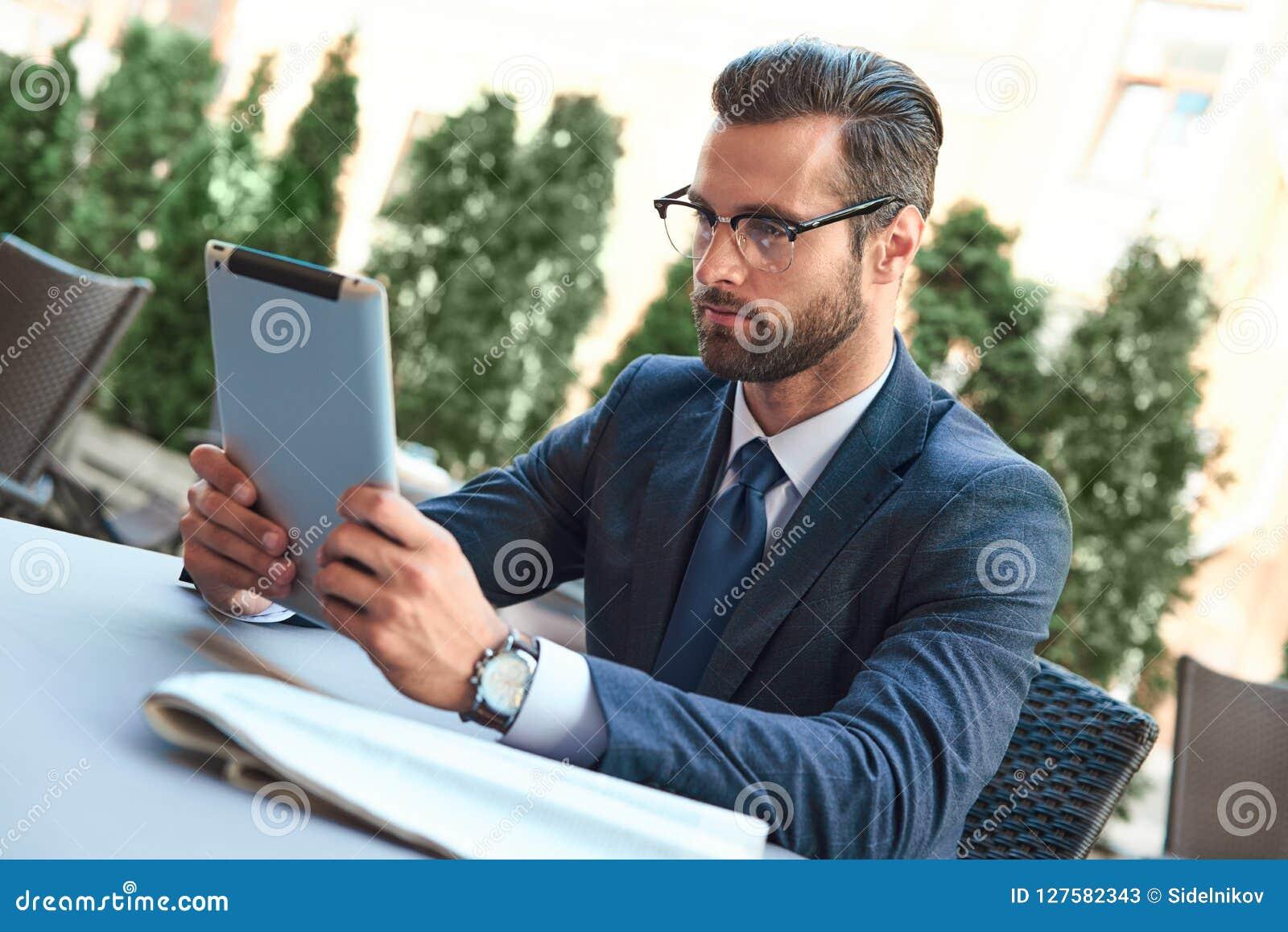 Молодой бизнесмен с бородой и нося стеклами сидящ и смотрящ таблетка