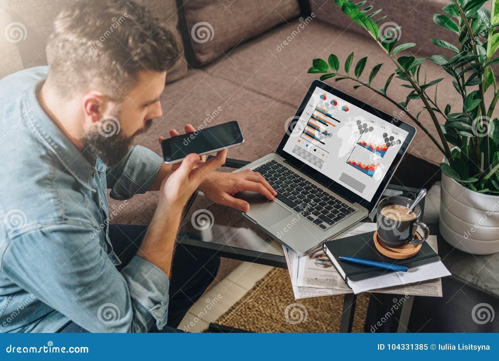 Молодой бородатый человек битника, предприниматель сидит на кресле на журнальном столе, использует компьтер-книжку с диаграммами,