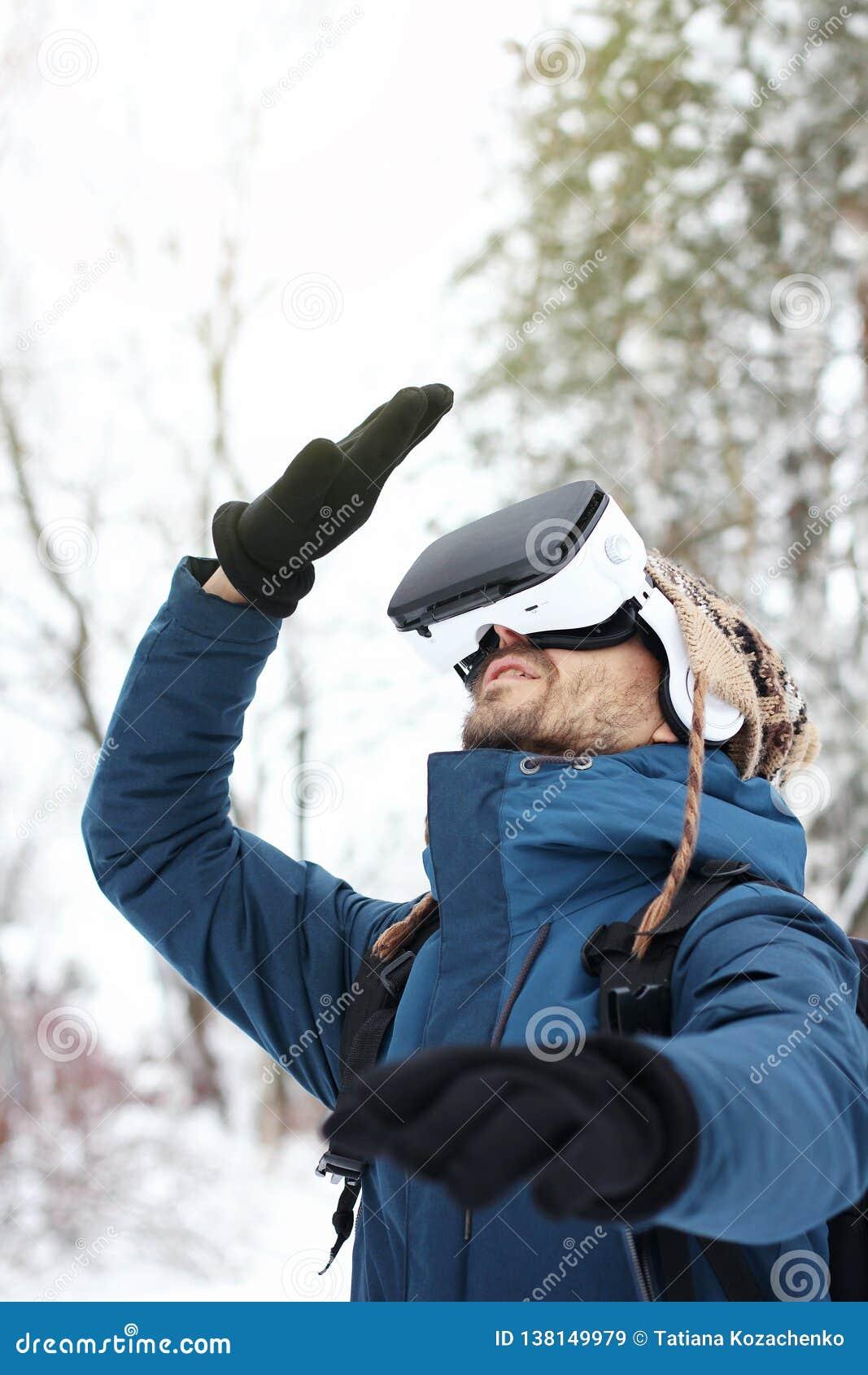 Молодой бородатый человек в связанной шляпе, теплой куртке и перчатках смотрит вверх использующ виртуальные стекла виртуальной ре