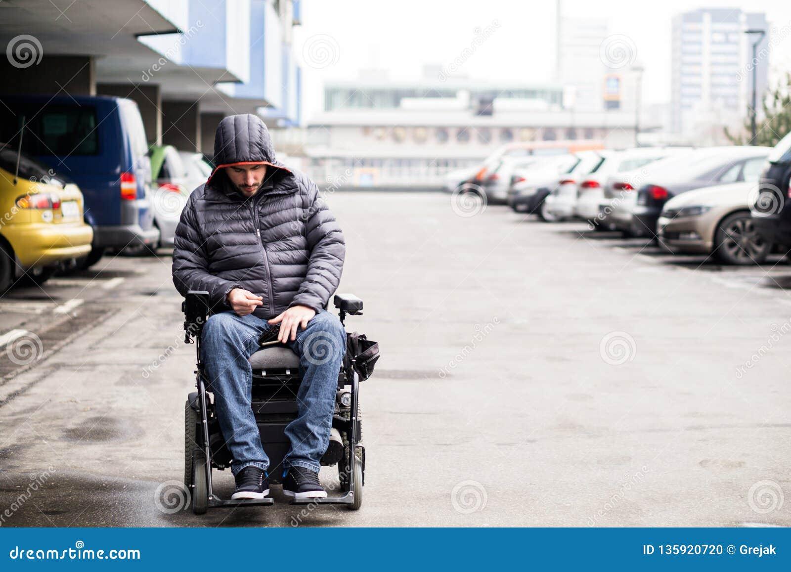 Молодой, взрослый человек в инвалидной коляске на парковке с космосом экземпляра
