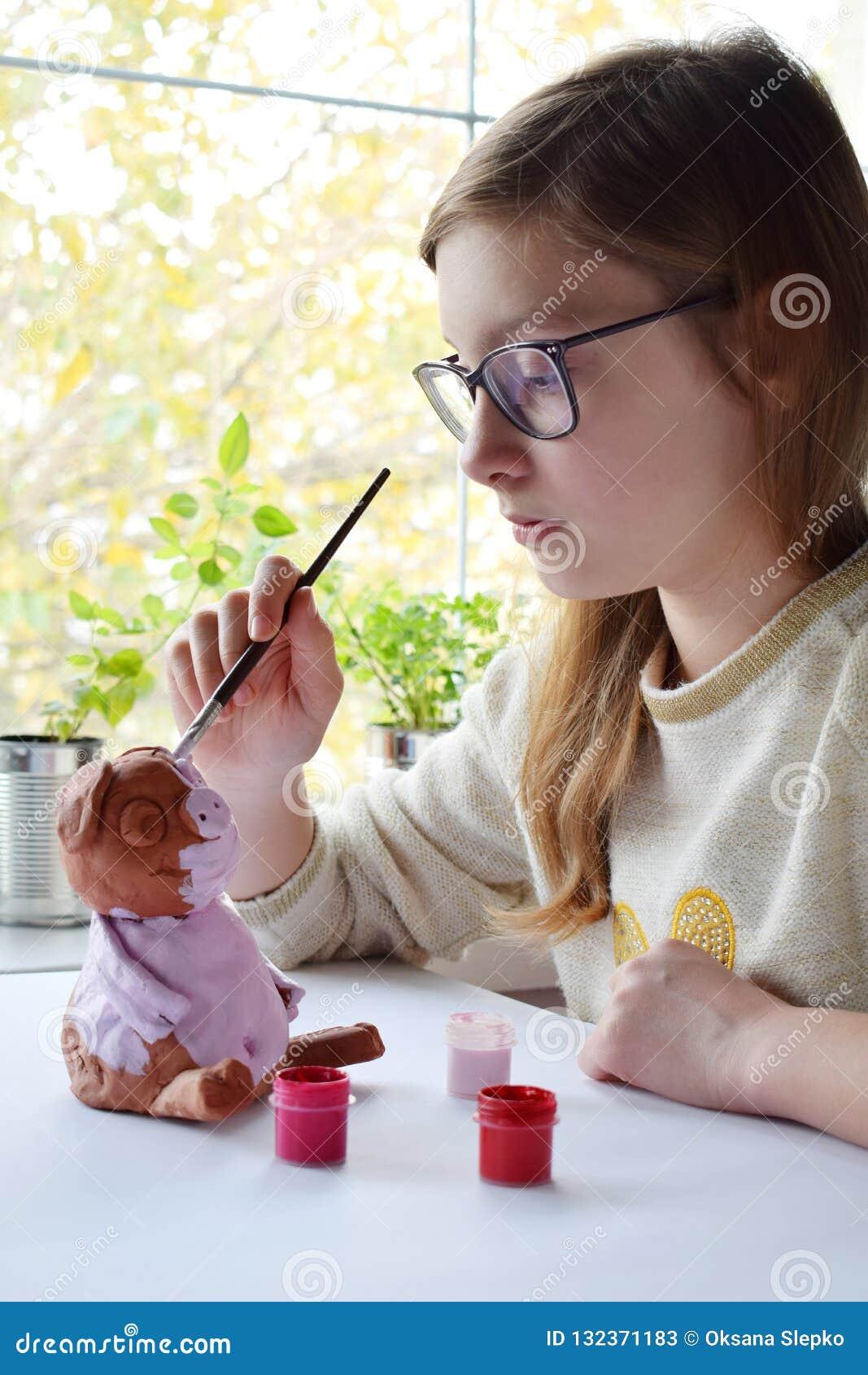 Молодой девочка-подросток делает игрушку, красит свинью глины с гуашью Творческий отдых для детей Поддерживая творческие способно