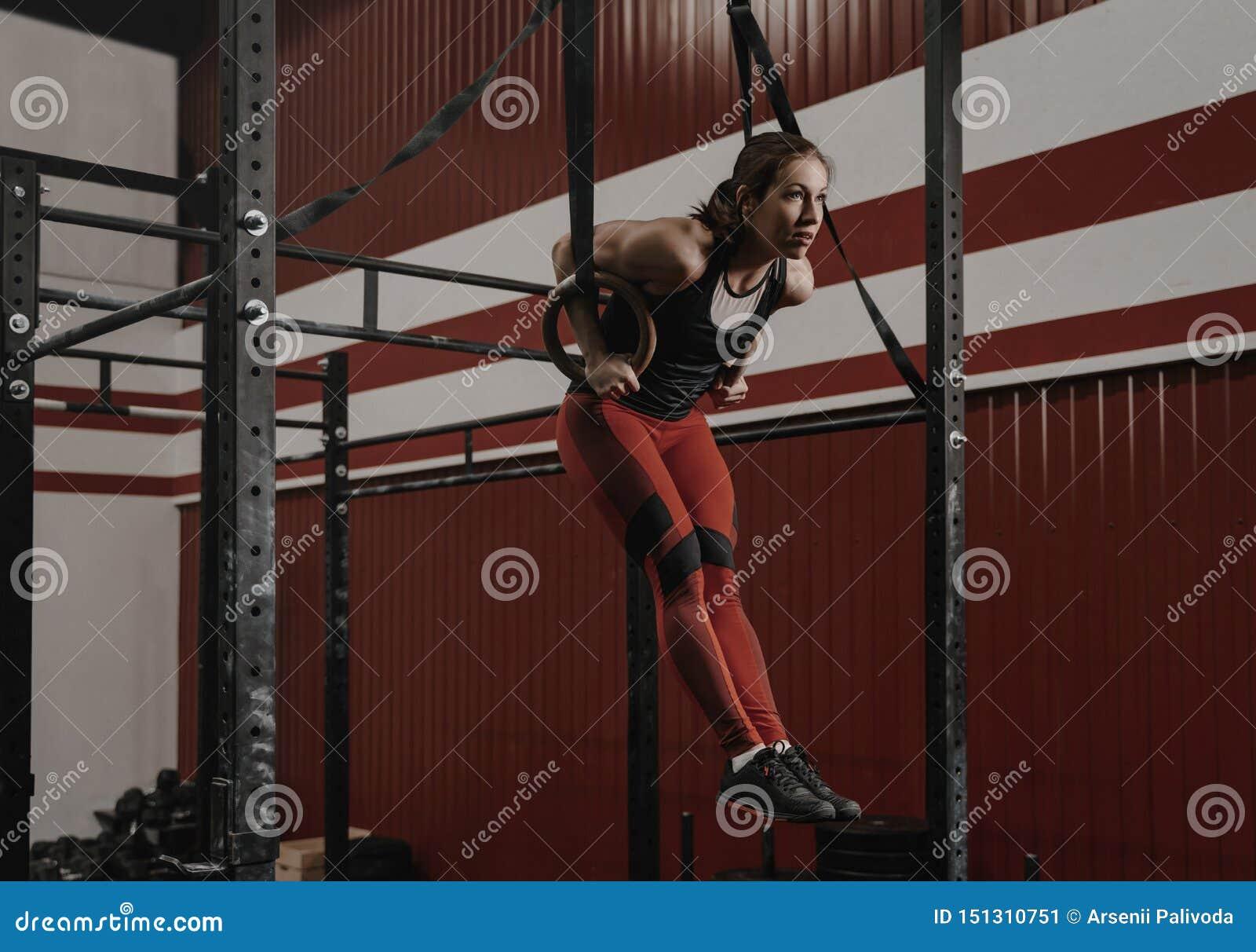 Молодой делать женщины crossfit мышц-поднимает на гимнастических кольцах на спортзале