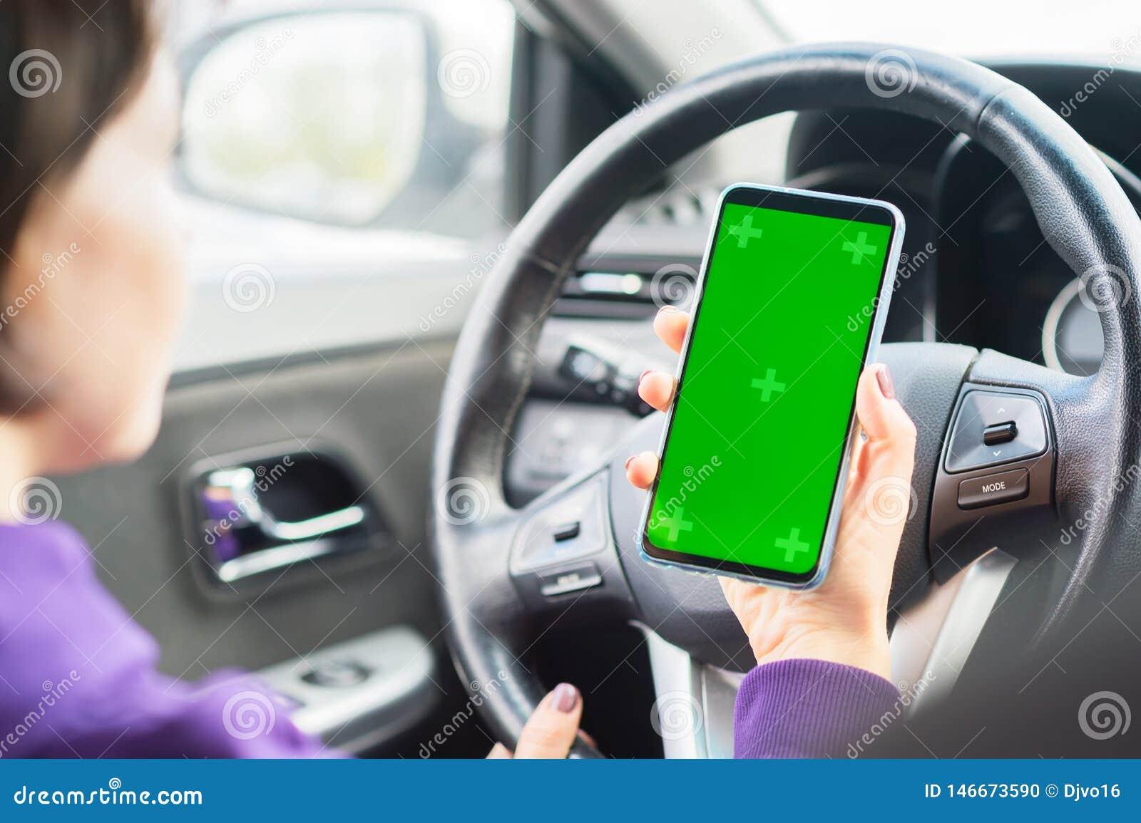Молодой женский водитель используя смартфон экрана касания в автомобиле зеленый ключ chroma на дисплее телефона