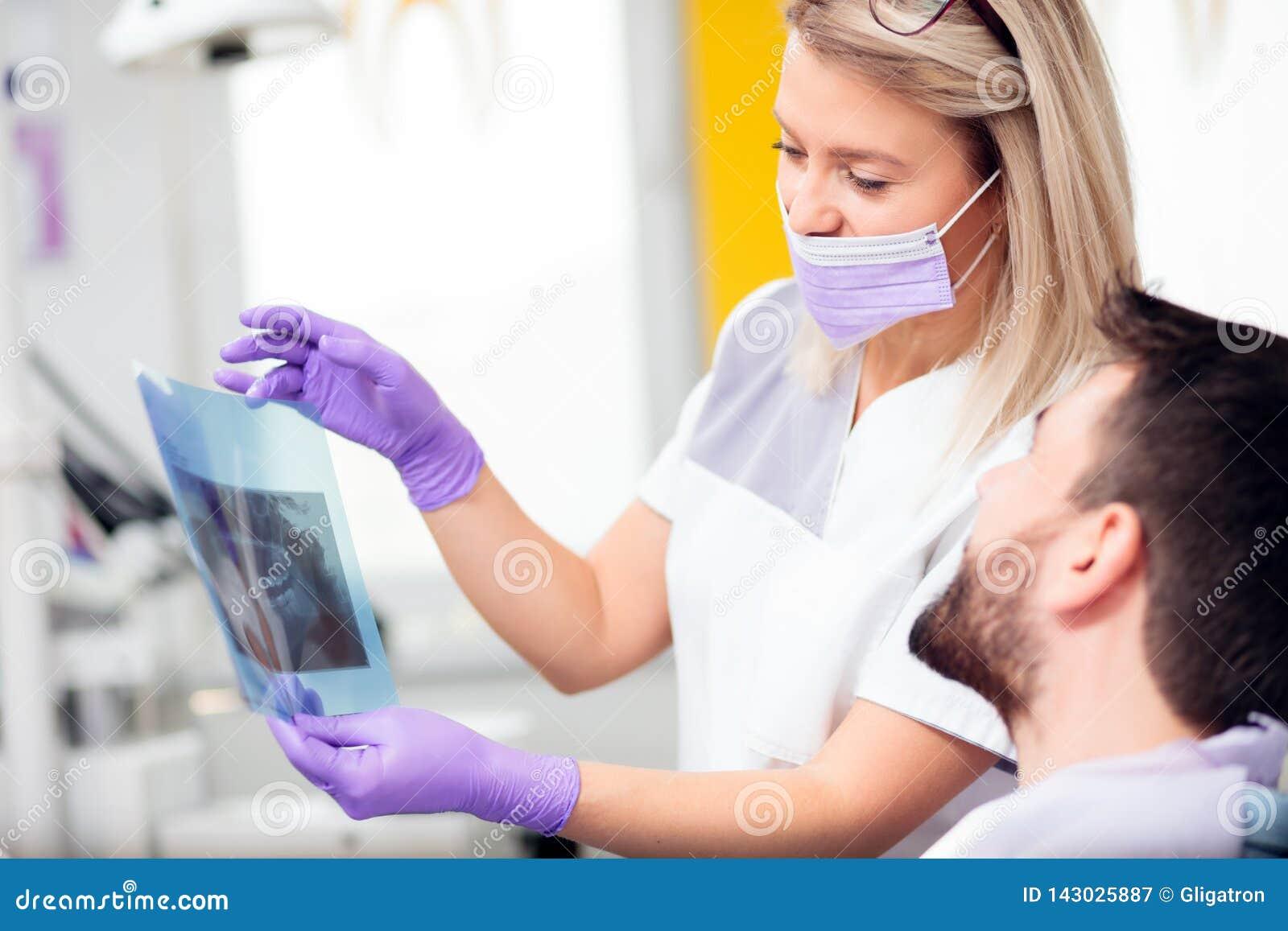 Молодой женский дантист показывая изображение рентгеновского снимка к мужскому пациенту после успешной интервенции