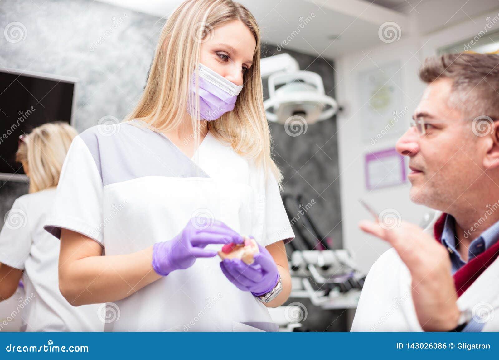 Молодой женский зубоврачебный техник советуя с со зрелым мужским доктором в зубоврачебной клинике