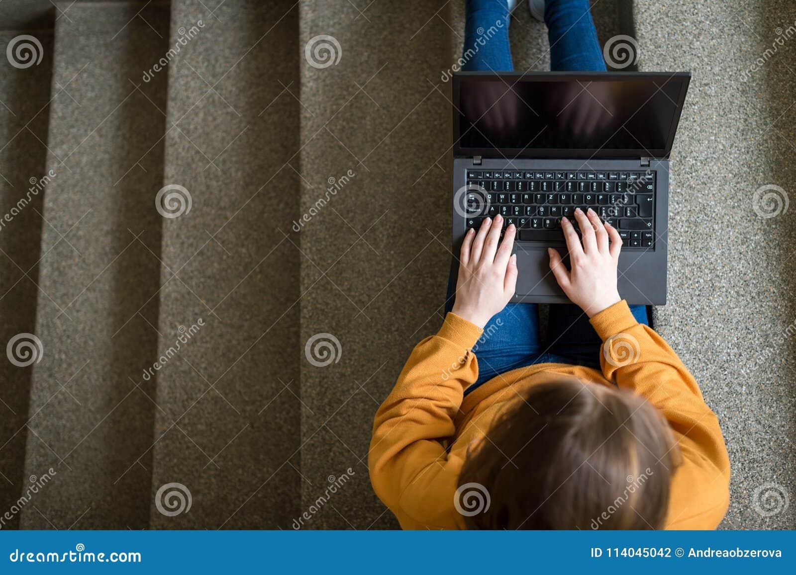 Молодой женский студент колледжа сидя на лестницах на школе, писать эссе на ее компьтер-книжке записывает старую принципиальной с
