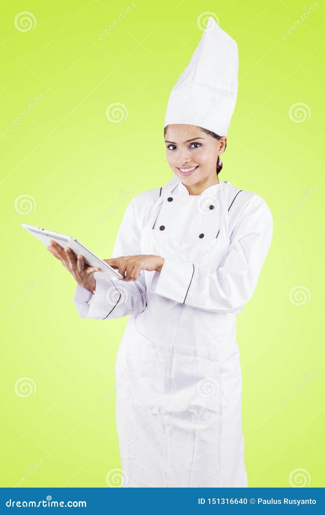 Молодой женский шеф-повар используя планшет в студии
