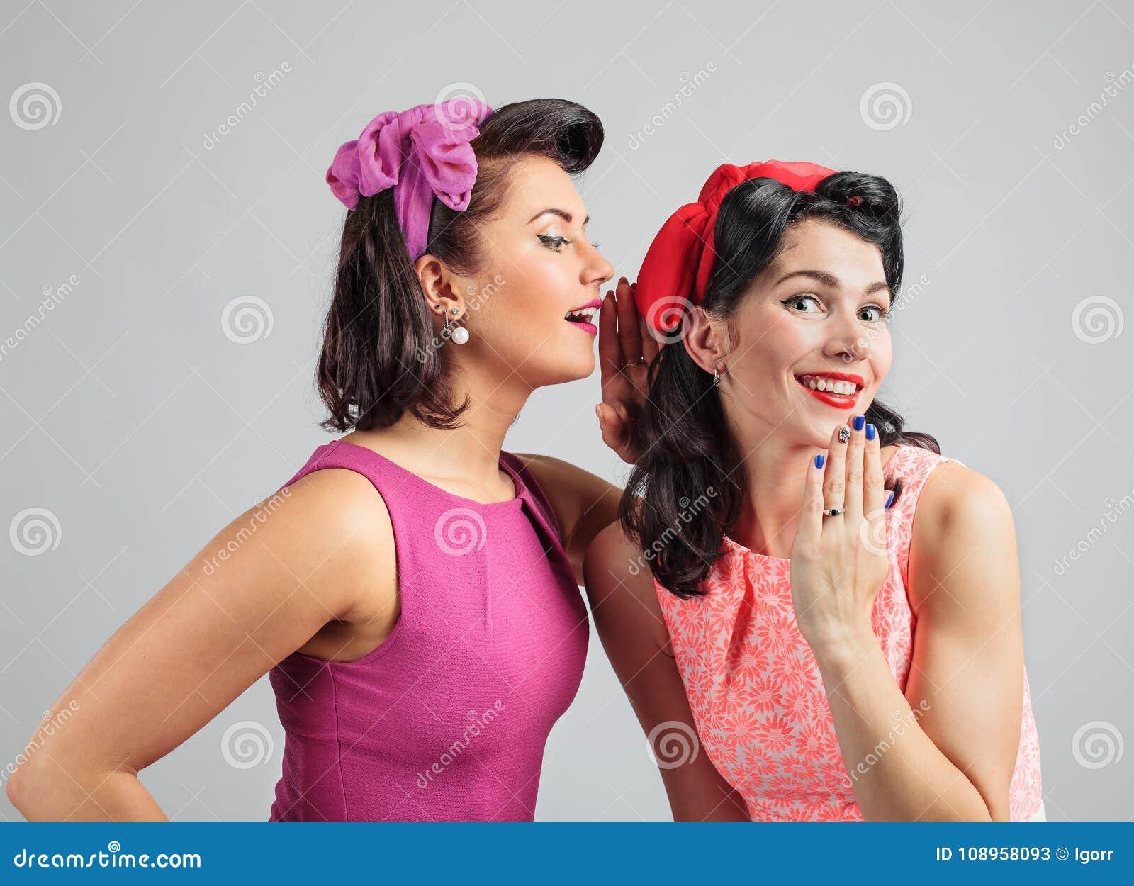 2 молодой женщины шепча сплетне