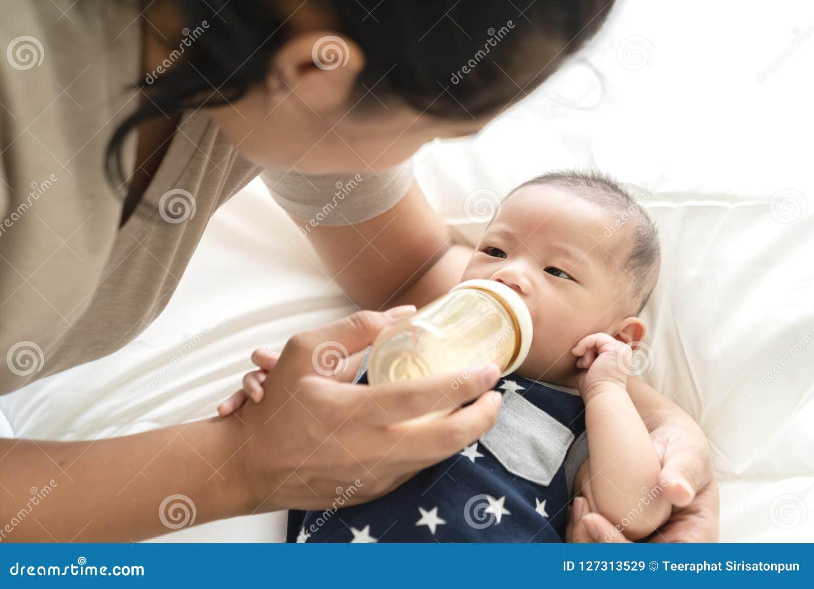 Молодой испанский младенец или азиатское младенческое питьевое молоко мальчика от пластичной бутылки - подающ от молодых родителе