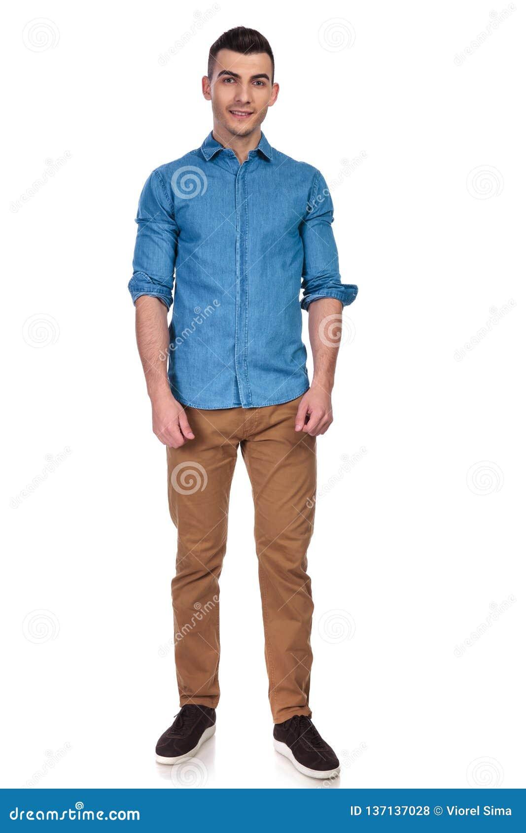 Молодой и красивый человек нося голубое положение рубашки