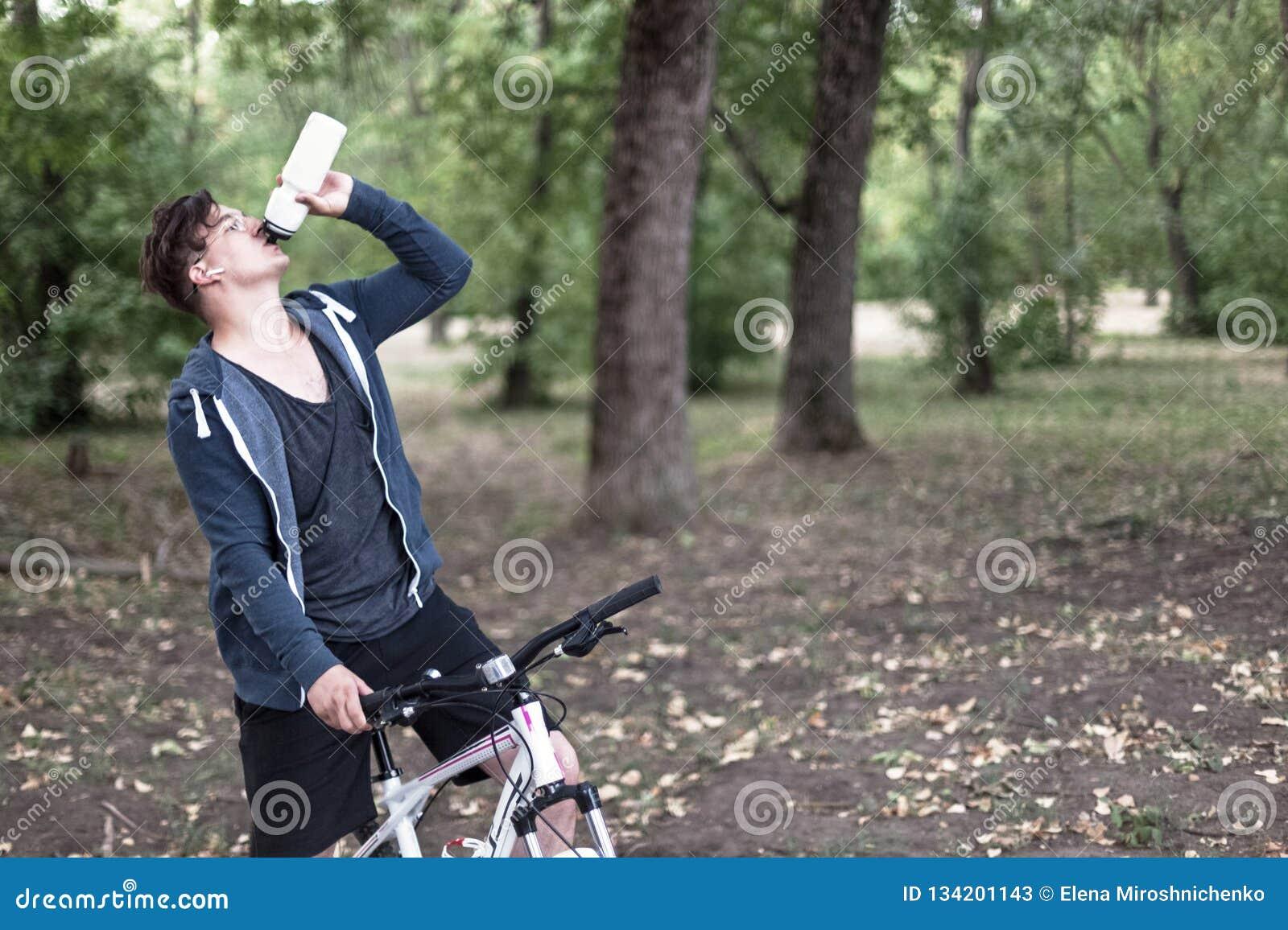 Молодой кавказский человек выпивает воду bicycling в парке