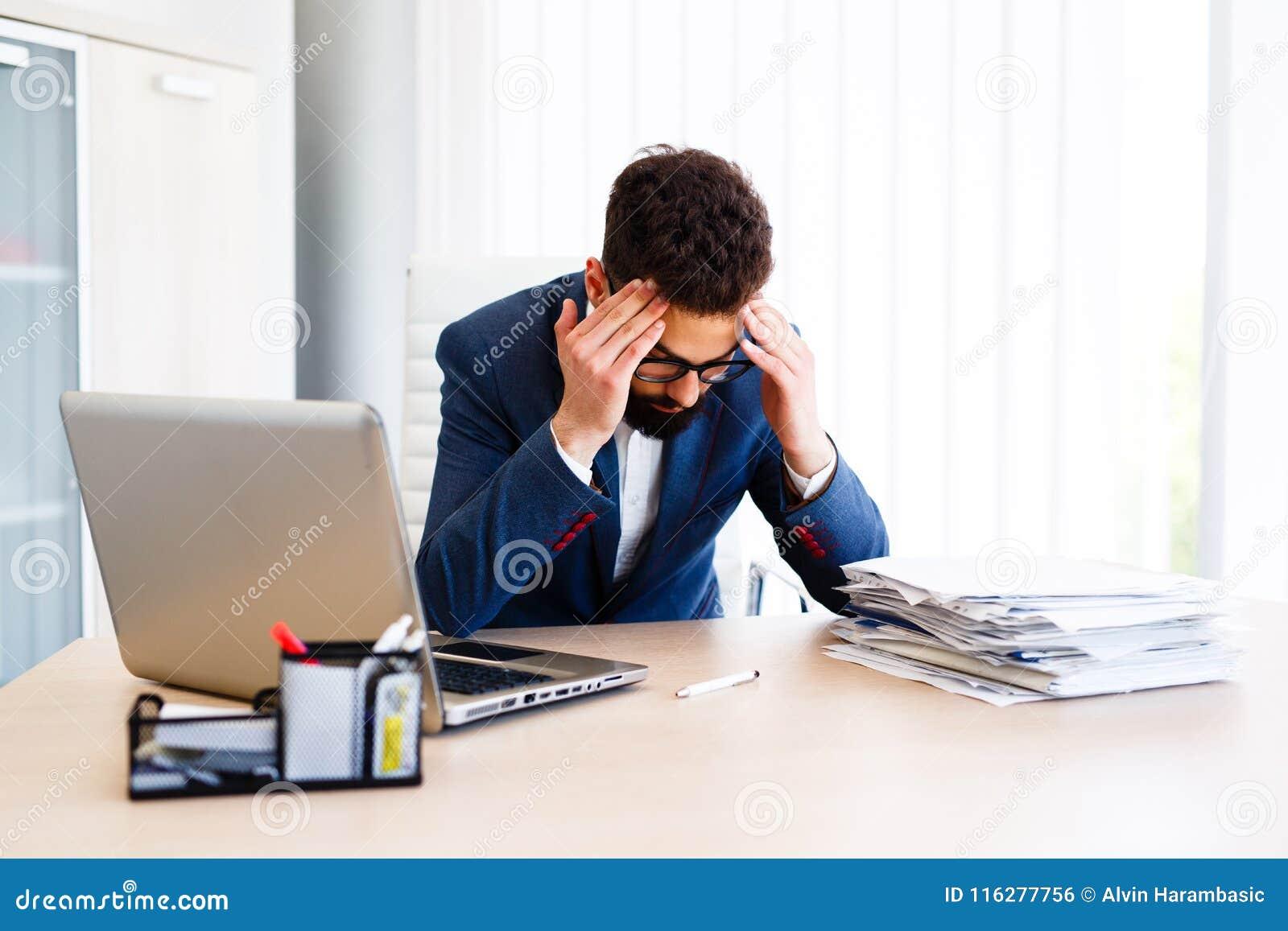 Молодой красивый бизнесмен имеет головную боль