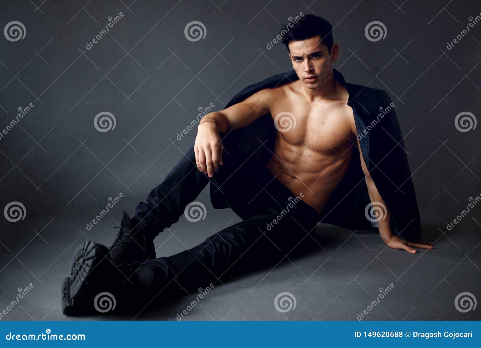 Молодой, красивый, сексуальный человек с курткой на его плечах, на нагом торсе, представляя усаживание на серой предпосылке, совр