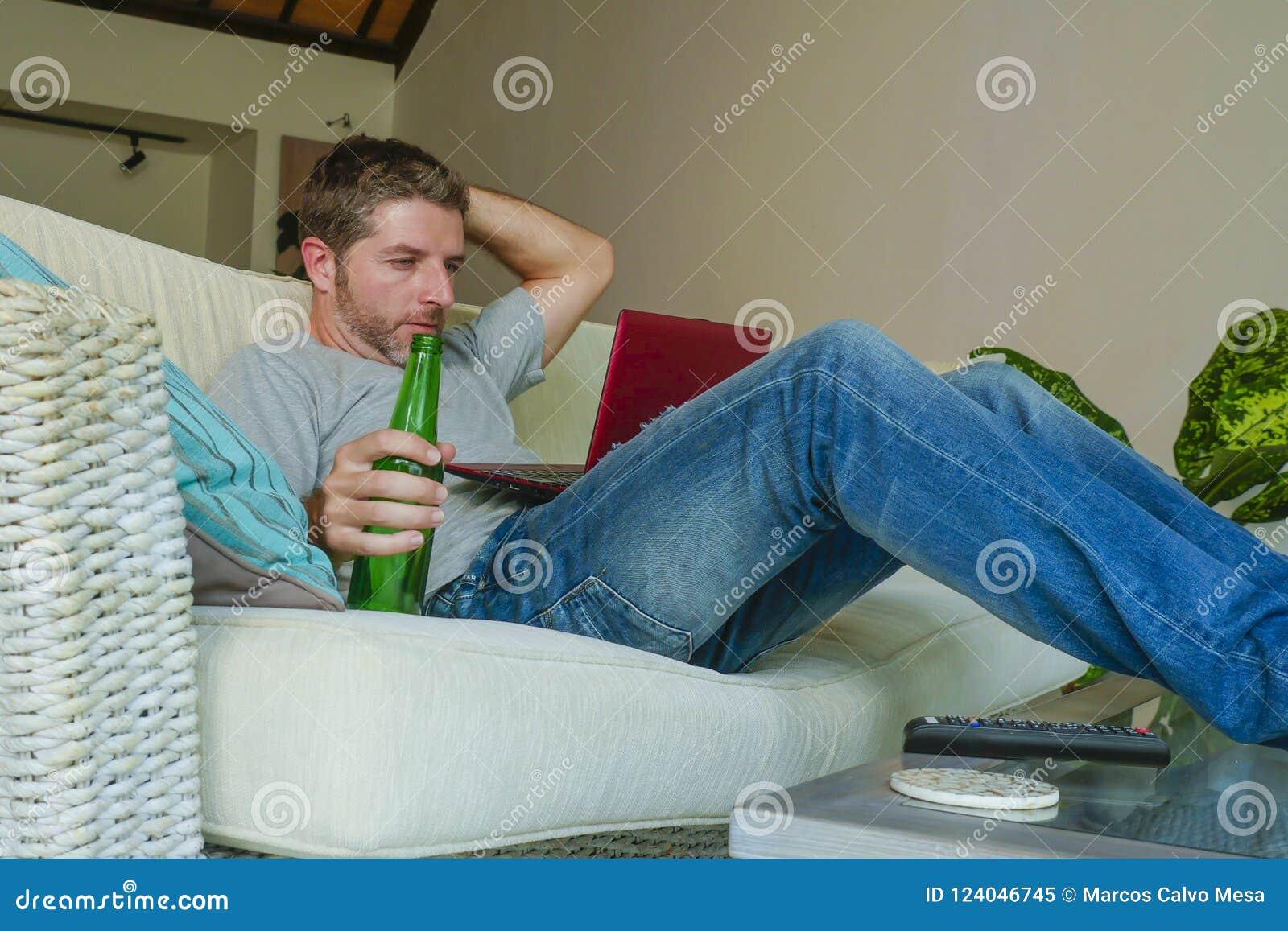 Молодой красивый счастливый человек сидя дома работа кресла софы онлайн с портативным компьютером используя netbook ослабил удобн