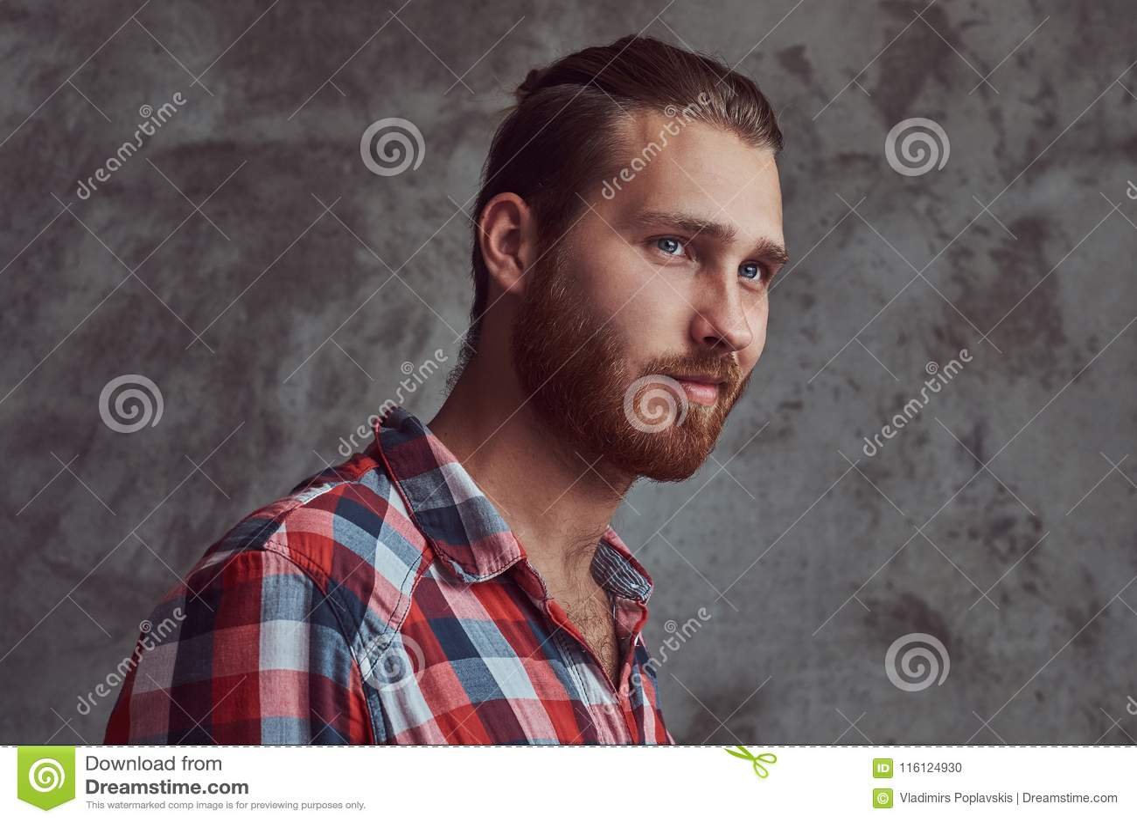 Молодой красивый человек модели redhead в рубашке фланели на серой предпосылке