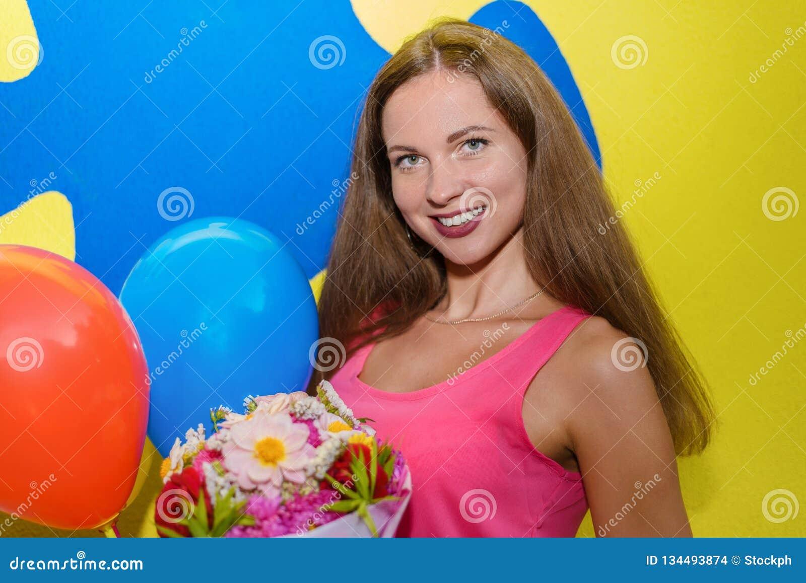 Молодой милый брюнет девушки усмехаясь и держа букет подачи