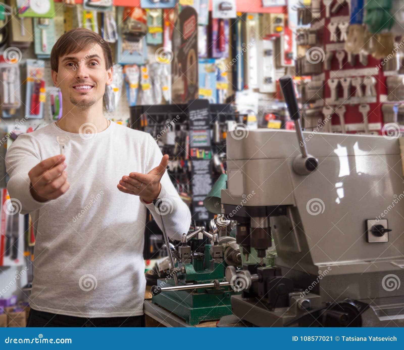 Молодой мужской продавец представляя с ключом