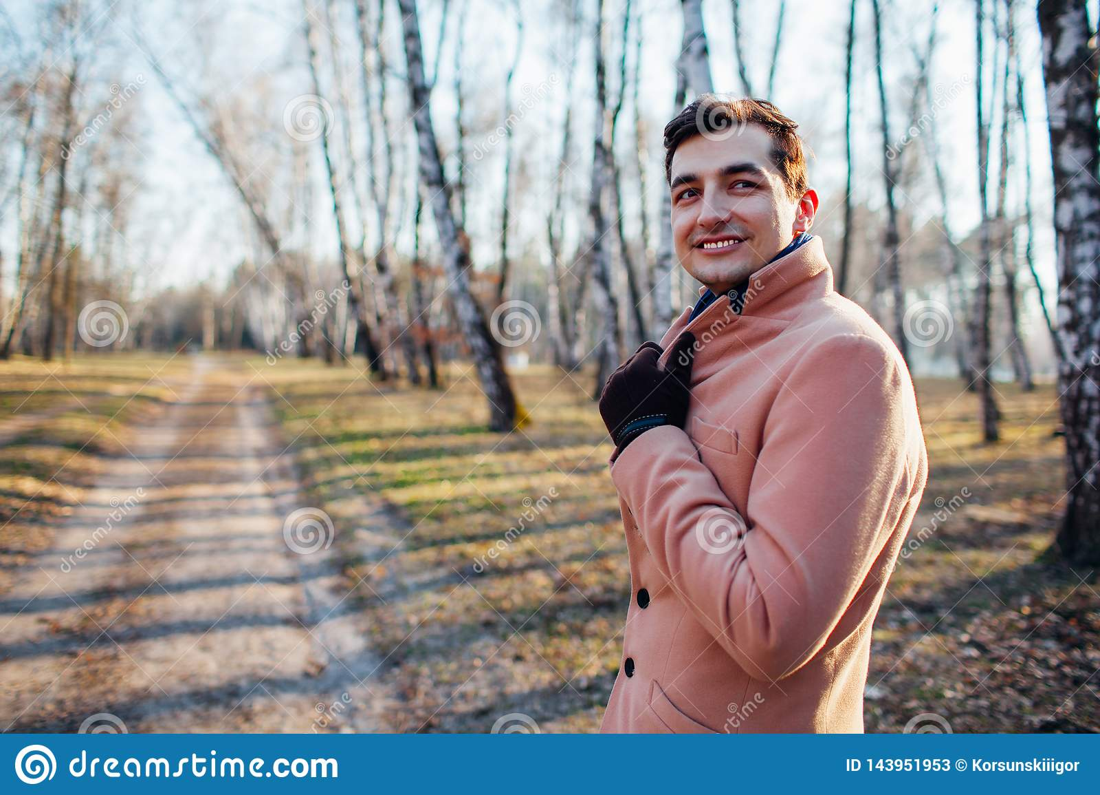 Молодой мужчина идя в лес в природе в пальто сливк