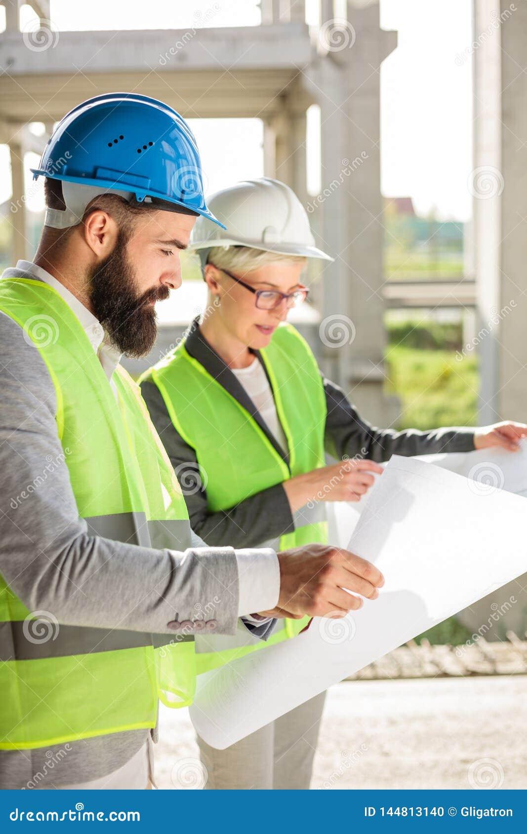 Молодой мужчина и женские архитекторы или деловые партнеры смотря планы здания на строительной площадке