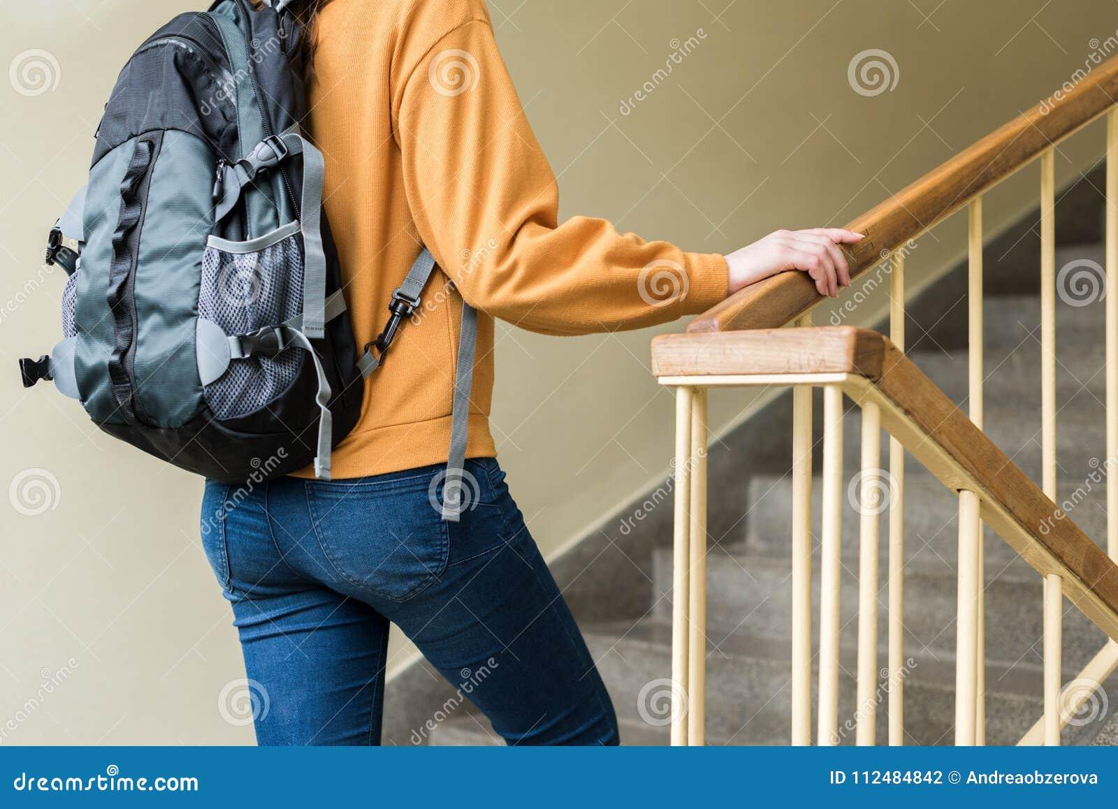 Молодой непознаваемый подавленный сиротливый женский студент колледжа идя вверх по лестницам на ее школе