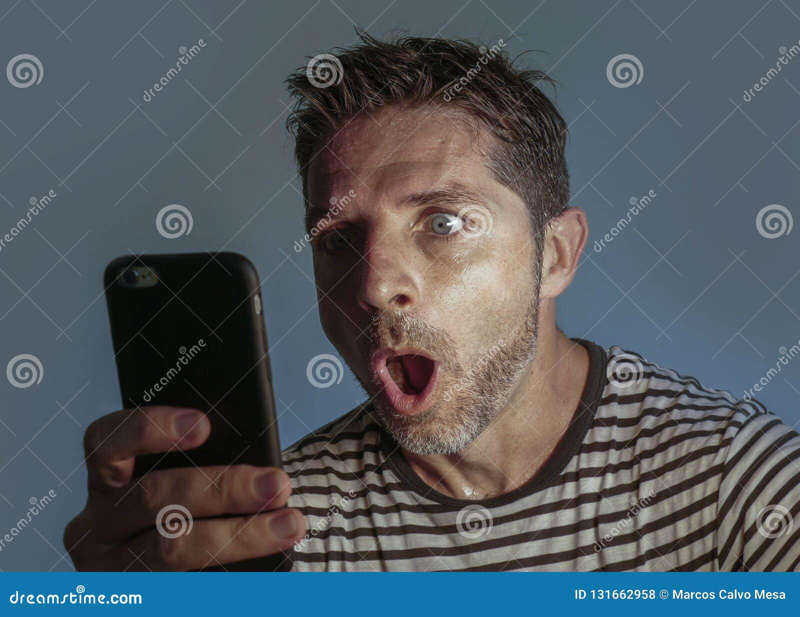 Молодой озадаченный и сотрясенный человек используя мобильный телефон смотря средства массовой информации интернета социальные ил
