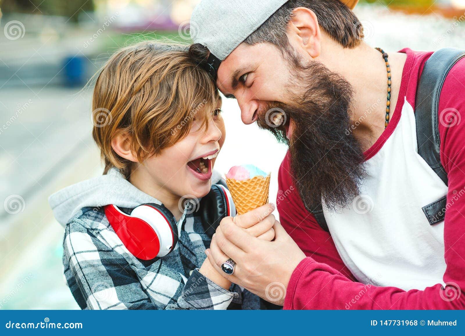 Молодой отец и сын наслаждаясь мороженым и имея потеху совместно Счастливая эмоциональная семья outdoors Каникулы, лето, идя на