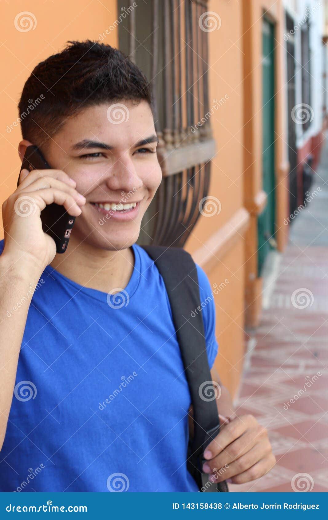 Молодой парень вызывая по телефону outdoors