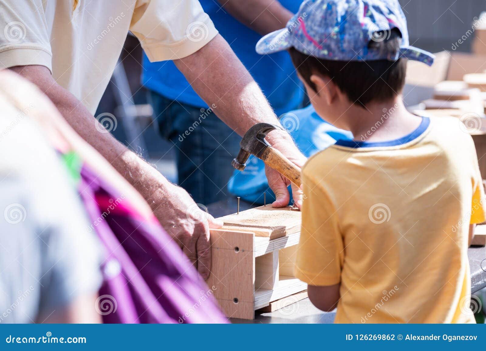 Молодой парень держа дом птицы здания молотка