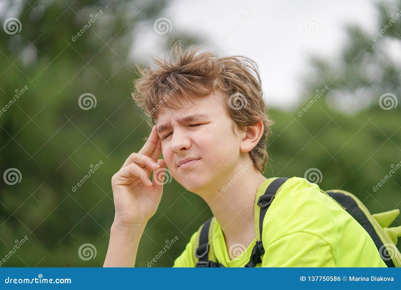 Молодой парень подростка страдает от головной боли он держит его руки к его голове и вздрагиваниям дискомфорта, сидя на природе
