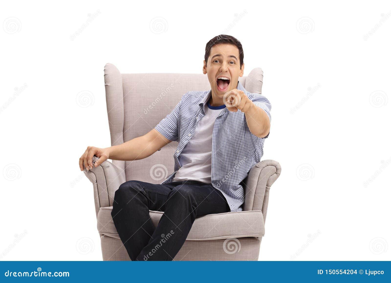 Молодой парень сидя в кресле указывая на камеру и смеясь вне громко