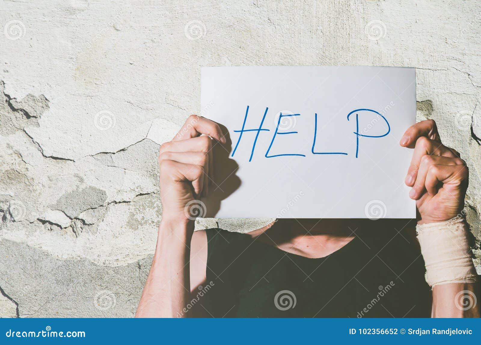 Молодой подавленный бездомный человек с повязкой на его руке от знака помощи удерживания попытки суицида написанного на бумаге по