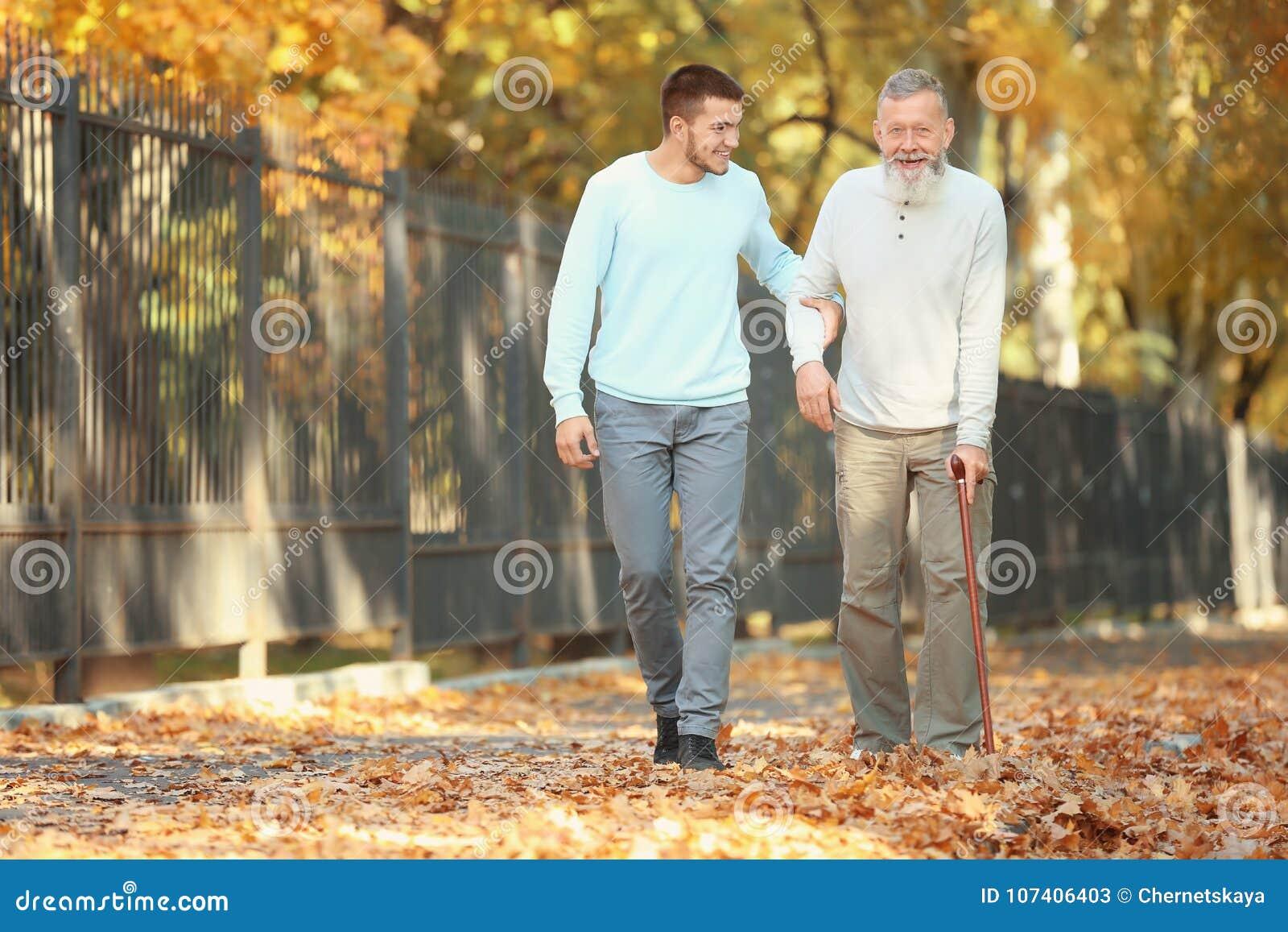 Молодой попечитель идя с старшим человеком