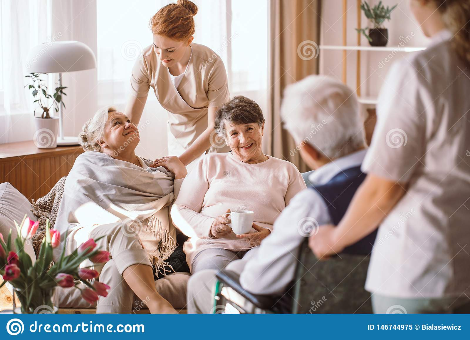 Молодой попечитель утешая пожилую женщину в доме престарелых