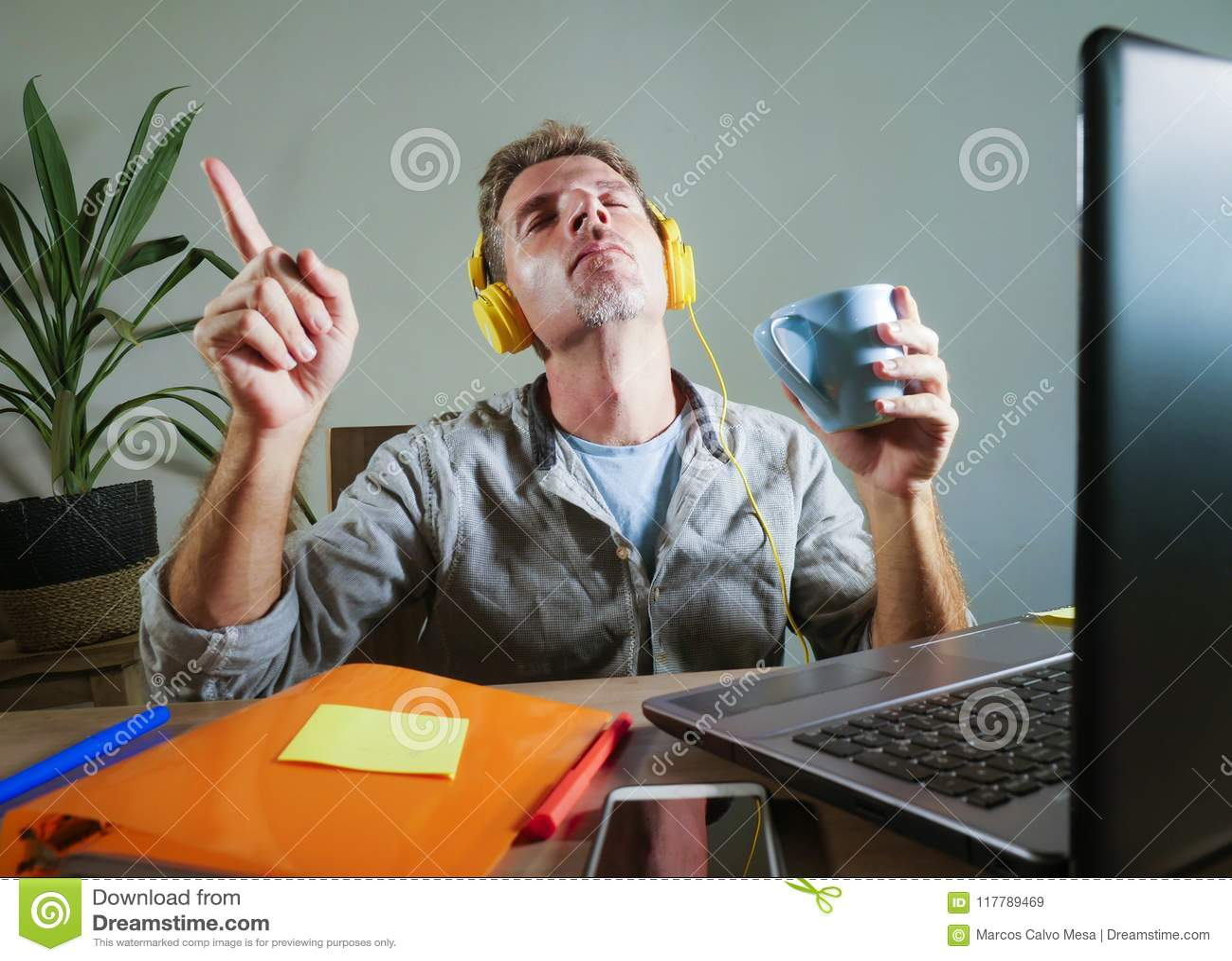 Молодой привлекательный и счастливый человек при желтые наушники сидя дома стол офиса работая при портативный компьютер имея list