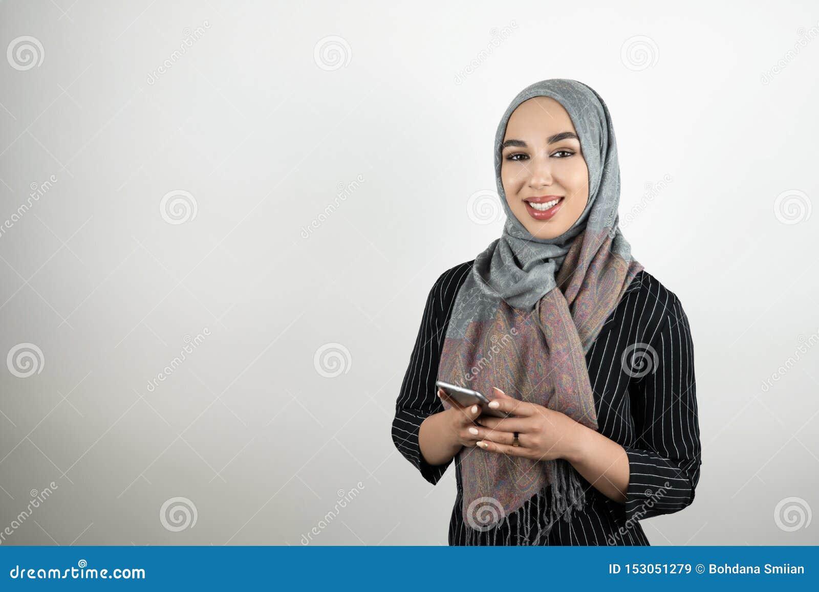 Молодой привлекательный усмехаясь смартфон удерживания головного платка hijab тюрбана мусульманской женщины нося в ее руках изоли
